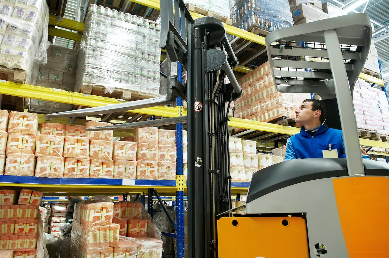 Food-grade warehouse worker operating forklift