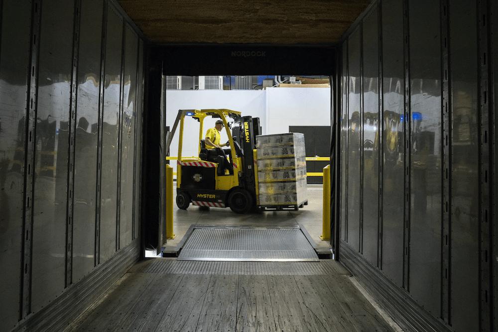 Forklift driving unloading beer cases off transport truck
