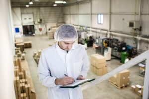 Man with a hairnet writing on a clipboard standing about a distribution center