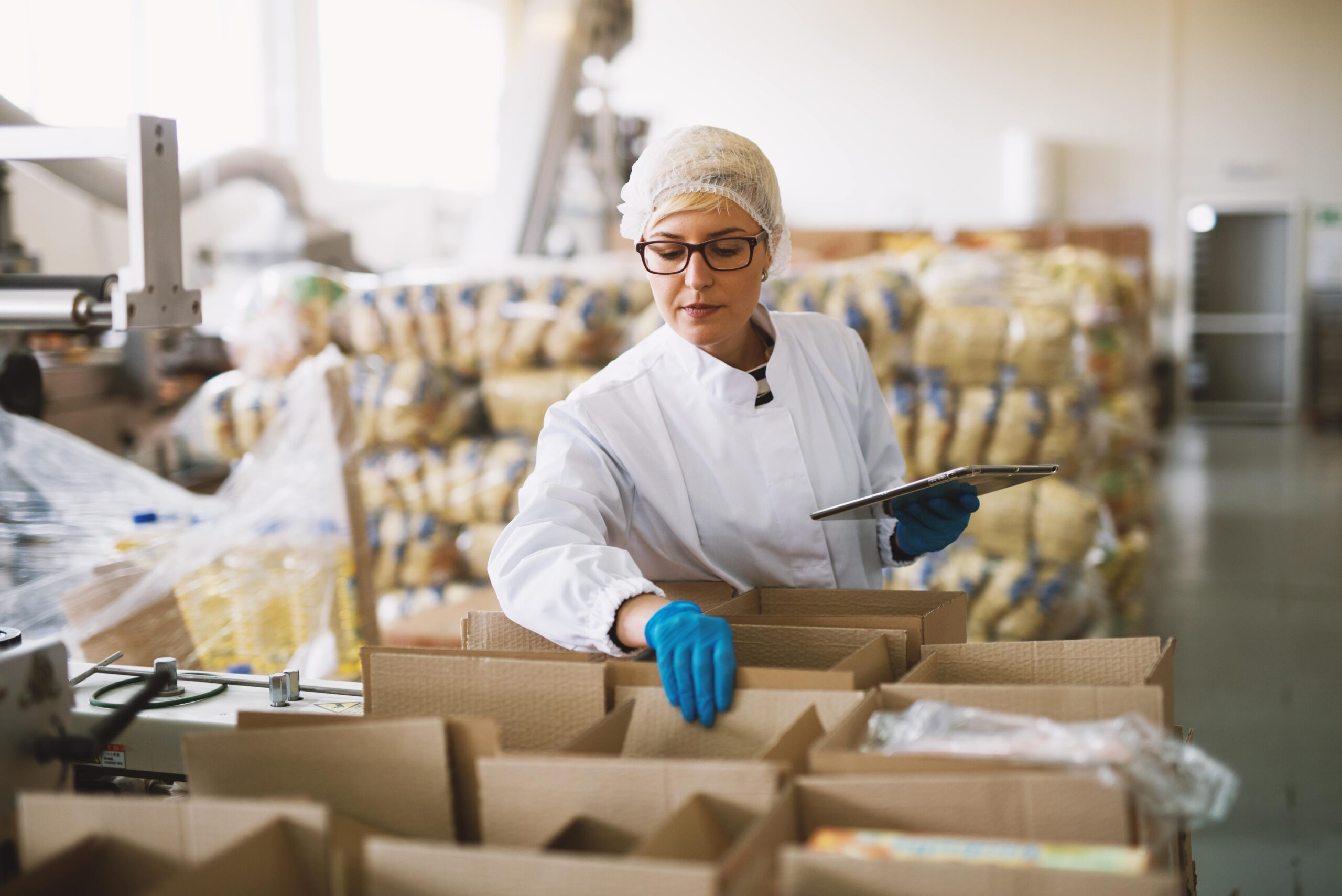 Lady holding tablet wearing blue gloves and lab coat checking boxes in a warehouse